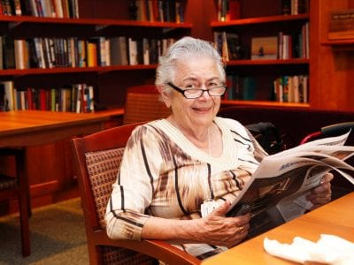 Woman smiling while reading paper in library.
