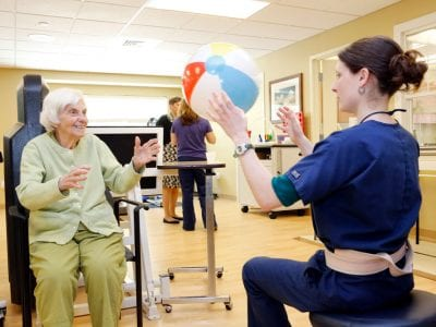 Women playing with beach ball in physical therapy.