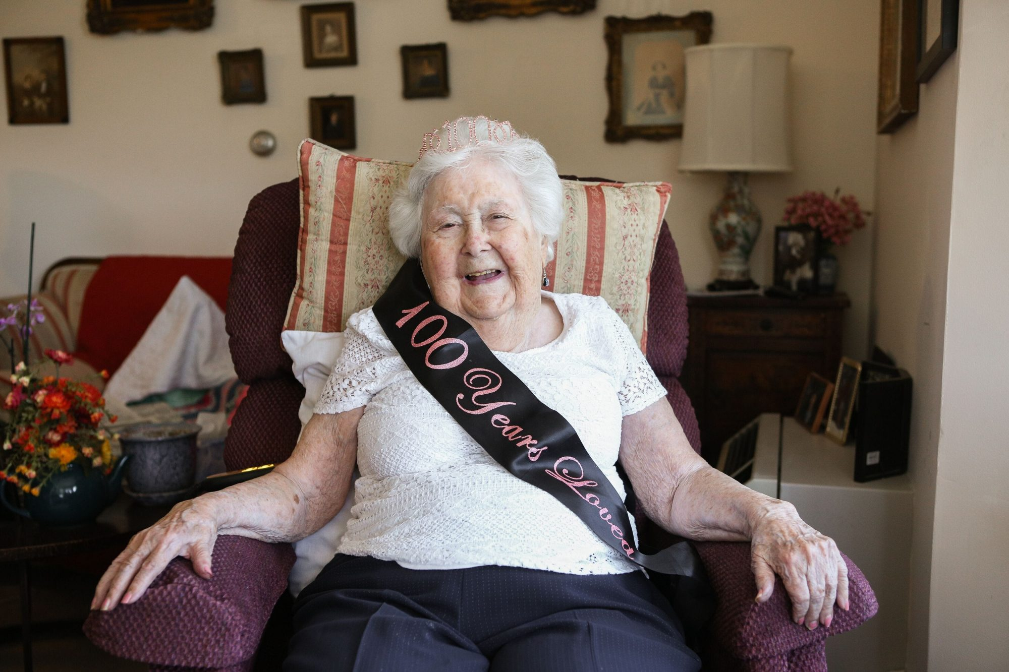 Resident Stasi Dunau with a sash and a tiara celebrating her 100th birthday