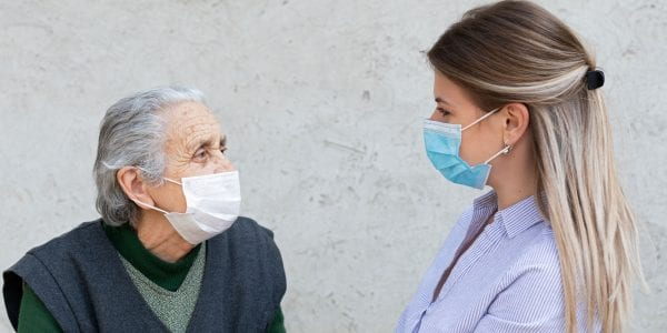 Older woman with young female caretaker, wearing masks