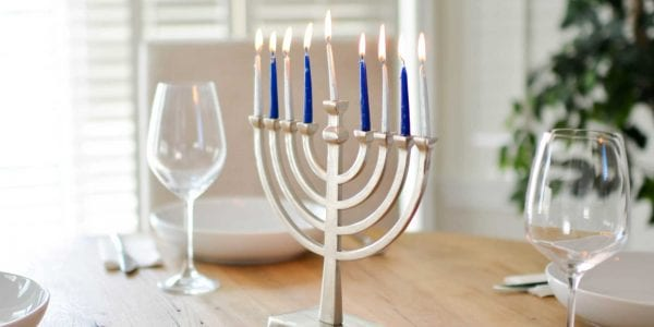 A lit menorah on a table with two place settings
