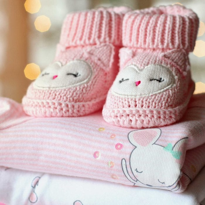 pink knit baby booties on a pile of baby clothes