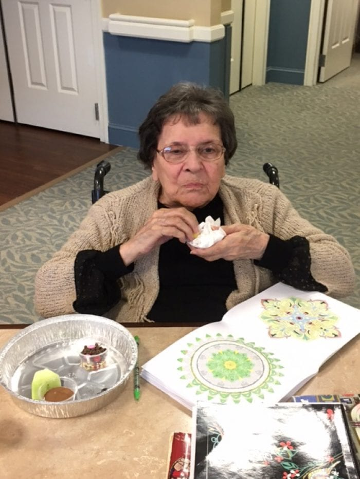 A resident of Brudnick Center for Living decorating and eating fruit