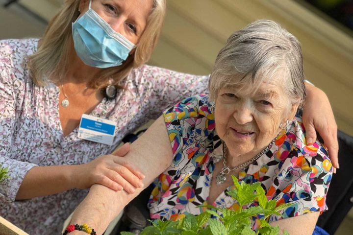 Susan LeClaire gardening with a resident.