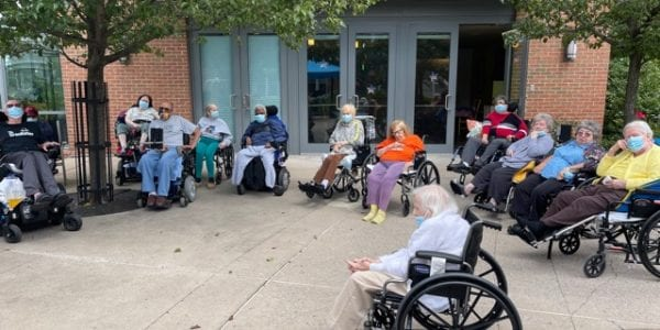 Residents of Leonard Florence Center for Living sit outside and enjoy the weather