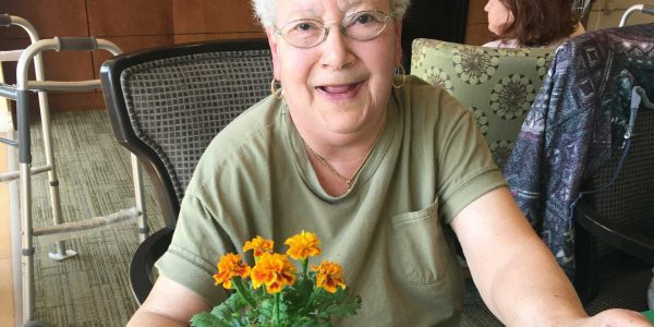 A resident with her flower arrangement