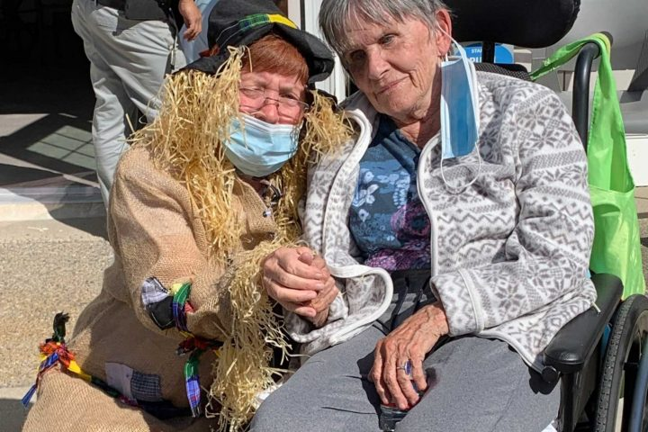 A resident with an employee dressed as a scarecrow at Harvest Fest.