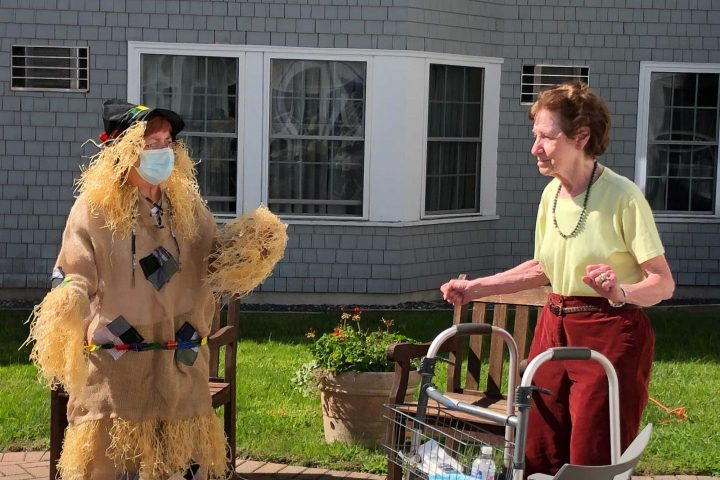 A resident enjoys dancing to music with an employee dressed as a scarecrow at Harvest Fest.