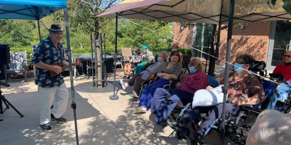 Residents sit outdoors and listen to live music